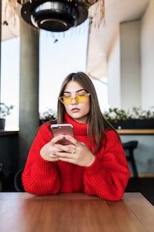 Afbeelding van jonge vrouw die sms leest aan de telefoon in café