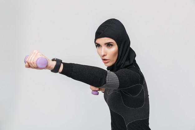 Afbeelding van jonge vrouw fitness moslim oefeningen maken met halters geïsoleerd.