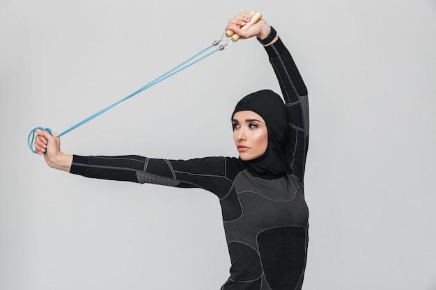 Afbeelding van jonge vrouw fitness moslim oefeningen maken met springtouw geïsoleerd.
