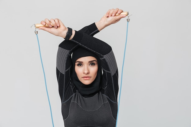 Afbeelding van jonge vrouw fitness moslim poseren geïsoleerd maken oefeningen met springtouw.