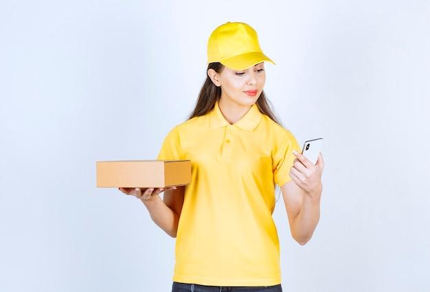Afbeelding van jonge vrouw met pakket en mobiele telefoon over witte muur.