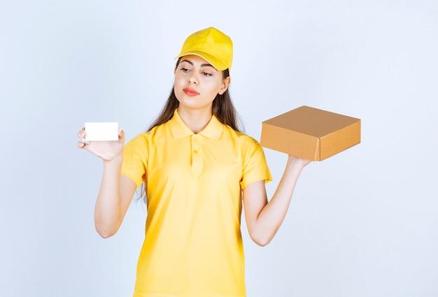 Afbeelding van jonge vrouw met pakket en visitekaartje over witte muur.