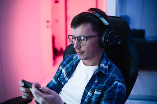 Afbeelding van kaukasische youngman in koptelefoon met behulp van mobiele telefoon spelen van videogame in een gaming-stoel thuis.