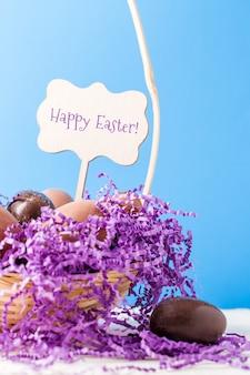 Afbeelding van kip, chocolade-eieren, paars decoratief papier in mand op lege blauwe muur met wens voor vrolijk pasen
