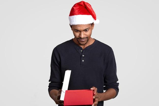 Afbeelding van knappe jonge man met donkere huid, kijkt verrassend naar geschenkdoos, draagt kerstmuts, gekleed in trui