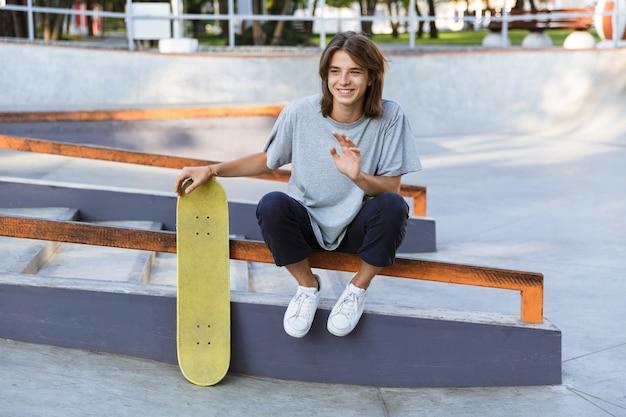 Afbeelding van knappe jonge skater man zitten in het park met skateboard.