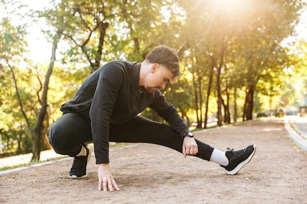 Afbeelding van knappe jonge sport fitness man loper buiten in park oefeningen maken.