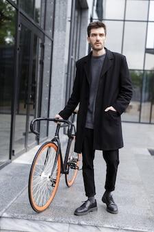 Afbeelding van knappe jonge zakenman buiten lopen met fiets.