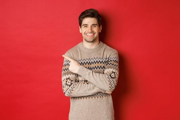 Afbeelding van knappe man in kersttrui, nieuwjaarsvakantie vieren, gelukkig lachend en wijzende vinger naar de kopieerruimte in de linkerbovenhoek, staande op rode achtergrond