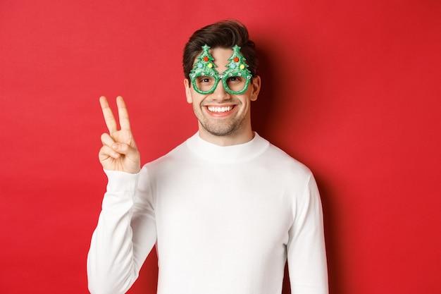 Afbeelding van knappe man in witte trui en feestbril, vredesteken tonend en glimlachen, vrolijk kerstfeest wensend, staande op rode achtergrond.