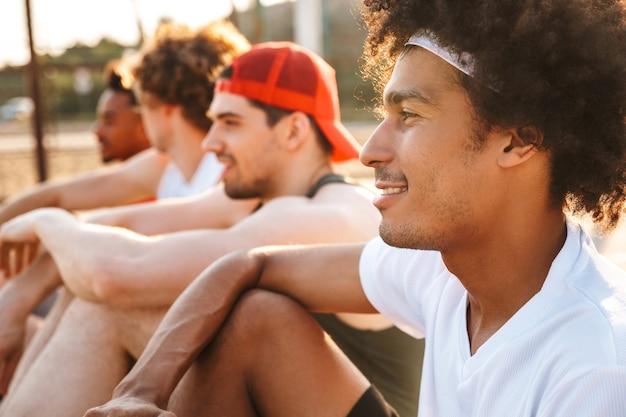Afbeelding van knappe mannen spelers zitten op basketbal speeltuin buiten, en kijken naar spel tijdens zonnige zomerdag