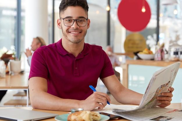Afbeelding van knappe tevreden man leest laatste nieuws in de krant, registreert enkele notities in kladblok, draagt een bril en t-shirt, geniet van heerlijke croissant. mensen en werkconcept