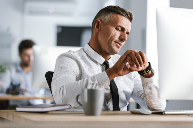 Afbeelding van knappe zakenman 30s dragen wit overhemd en stropdas zitten aan de balie in kantoor door computer, en kijken naar polshorloge