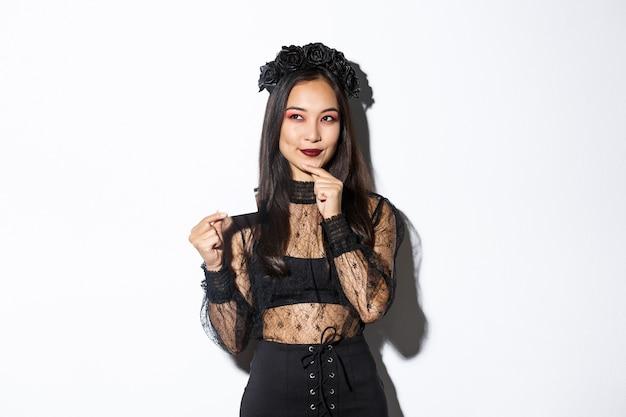 Afbeelding van lachende mooie aziatische vrouw in gotische kanten jurk en krans, denken terwijl creditcard, staande op witte achtergrond.
