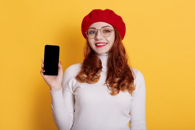 Afbeelding van lachende roodharige meisje met rode baret en wit overhemd, meisje met rode lippen met slimme telefoon met leeg scherm in handen op geel