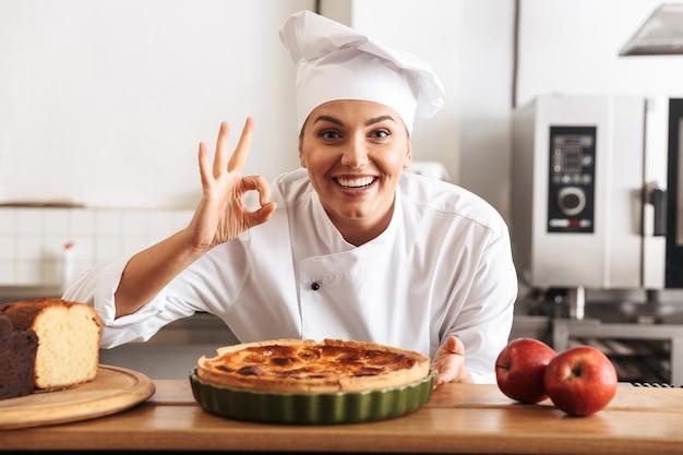 Afbeelding van lachende vrouw chef-kok dragen witte uniform, poseren in de keuken in het café met gebakken goederen