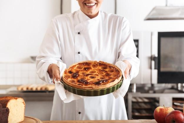 Afbeelding van lachende vrouw chef-kok dragen witte uniforme appeltaart houden, tijdens het koken in de keuken bij de bakkerij