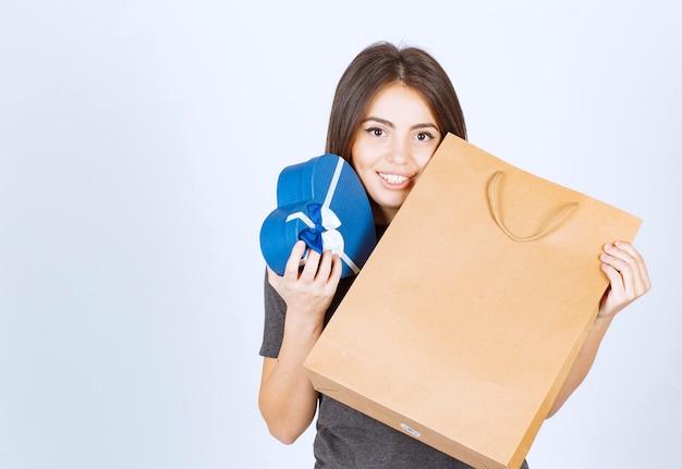 Afbeelding van lachende vrouw met een hartvormig geschenk en papieren zak in handen.