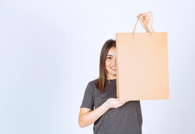 Afbeelding van lachende vrouw met een papieren zak en poseren.
