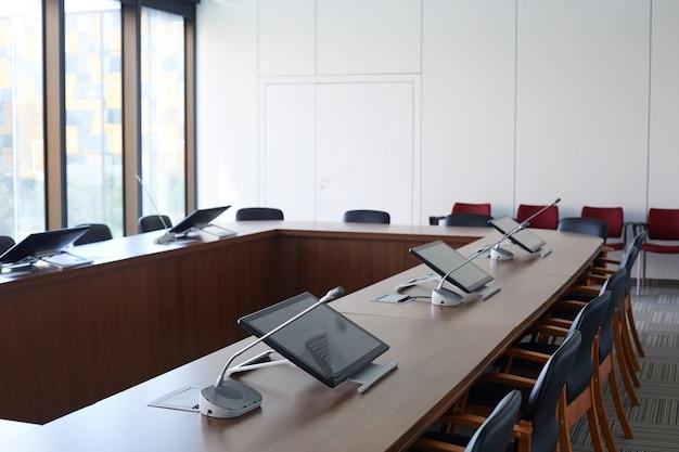 Afbeelding van lege directiekamer met computers op tafel in modern kantoorgebouw