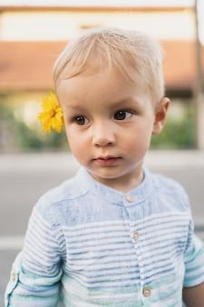 Afbeelding van lieve jongen, close-up portret van kind met een gele bloem in zijn haar