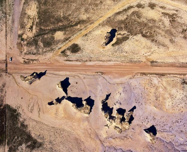 Afbeelding van luchtfoto van bovenaf van woestijn met onverharde weg en obelisk-rotsstructuren met auto voor perspectief