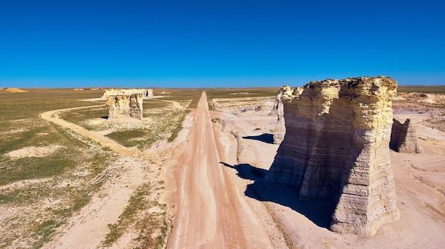 Afbeelding van luchtfoto van woestijnweg met grote witte rotspilaren