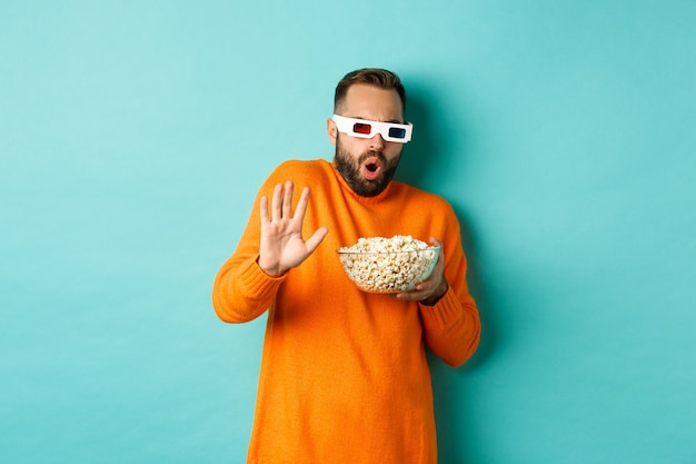 Afbeelding van man in 3d-bril kijken naar film, bang worden voor speciale effecten, met ontzag kijken, staande met popcorn tegen witte achtergrond.