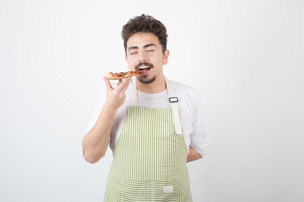 Afbeelding van mannelijke kok die een stuk pizza op wit eet