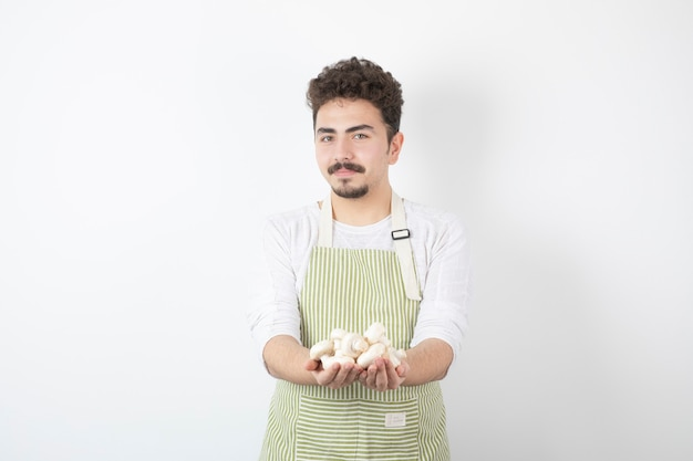 Afbeelding van mannelijke kok die rauwe champignons vasthoudt met serieuze uitdrukking