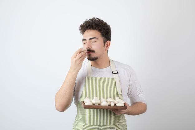 Afbeelding van mannelijke kok ruikt rauwe champignons op wit