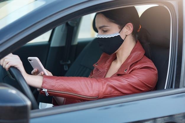 Afbeelding van meisje met donker haar en paardenstaart, leren jasje en beschermend masker, telefoon in handen houdend,