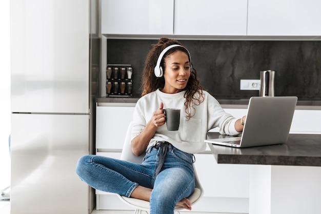 Afbeelding van moderne afro-amerikaanse meisje hoofdtelefoon dragen met behulp van laptop, zittend in lichte keuken