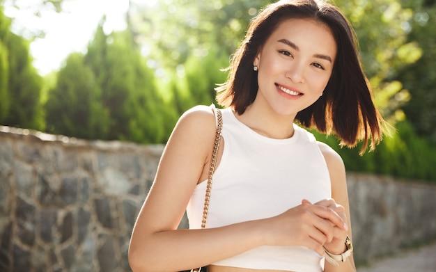 Afbeelding van moderne aziatische vrouw permanent in park en glimlachen