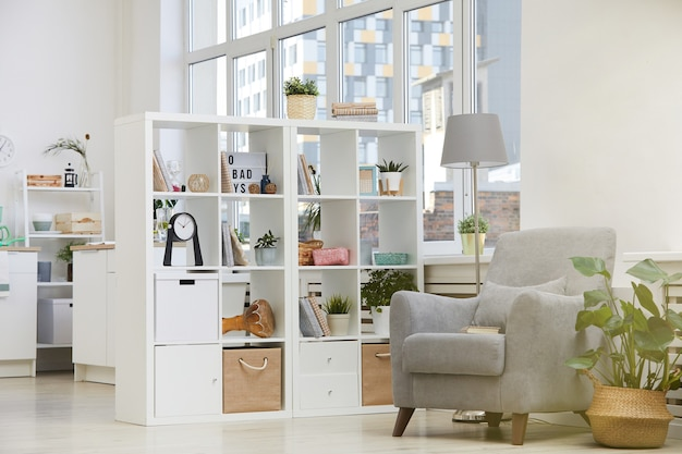 Afbeelding van moderne huiselijke kamer met fauteuil en boekenkast in huis