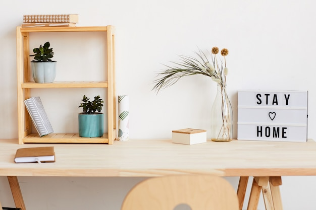 Afbeelding van moderne tafel met kladblok en bloemen erop thuis