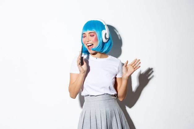 Afbeelding van mooi aziatisch meisje in blauwe pruik zingen in dynamische mobiele telefoon