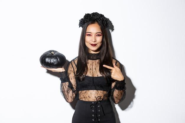 Afbeelding van mooie aziatische vrouw in gotische kanten jurk en krans wijzende vinger naar zwarte pompoen, halloween vieren, heks kostuum dragen, staande op witte achtergrond.