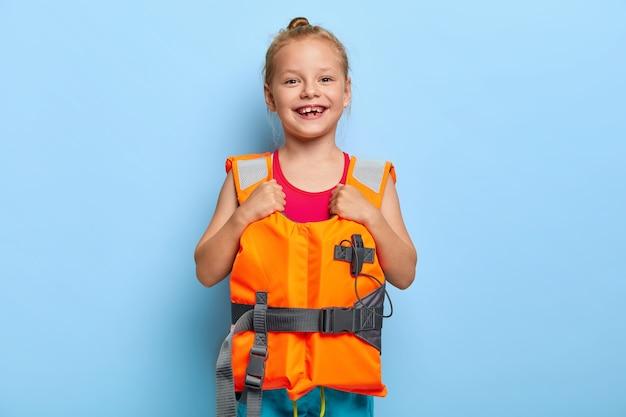 Afbeelding van mooie gember meisje draagt beschermende reddingsvest, geniet van veilige zomervakantie, favoriete seizoen