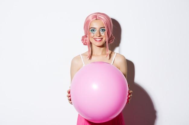 Afbeelding van mooie glamour meisje in roze pruik, grote ballon houden en glimlachen, vakantie vieren, permanent.