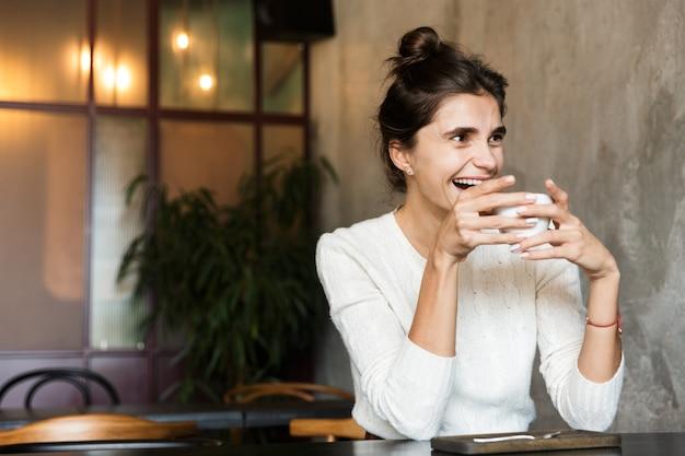 Afbeelding van mooie jonge vrouw zitten in café koffie binnenshuis drinken.