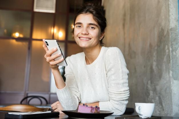 Afbeelding van mooie jonge vrouw zitten in café koffie drinken binnenshuis met behulp van chatten met mobiele telefoon.