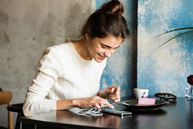 Afbeelding van mooie jonge vrouw zitten in café koffie drinken binnenshuis met behulp van mobiele telefoon luisteren muziek met koptelefoon.