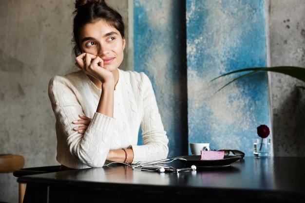 Afbeelding van mooie jonge vrouw zitten in café koffie drinken binnenshuis met behulp van mobiele telefoon.