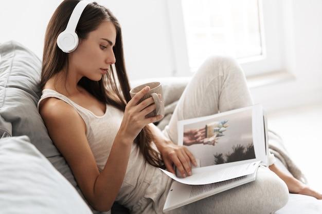 Afbeelding van mooie jonge vrouw zittend op de bank binnenshuis thuis luisteren muziek met koptelefoon drinken thee tijdschrift lezen.