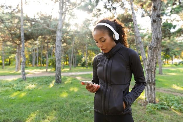 Afbeelding van mooie vrouw 20s dragen zwarte trainingspak en koptelefoon, met behulp van mobiele telefoon tijdens het wandelen door groen park