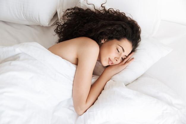 Afbeelding van mooie vrouw 20s met donker krullend haar, liggend in bed op een kussen en slapen op wit linnen
