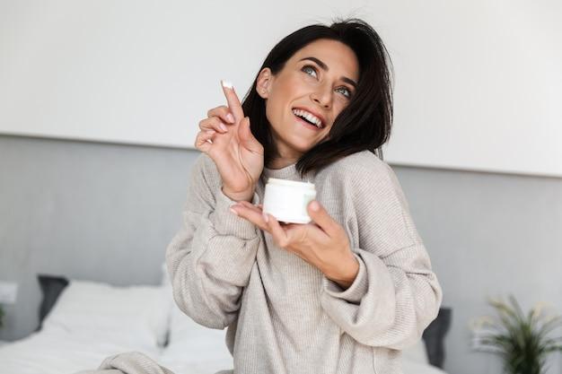 Afbeelding van mooie vrouw 30s pot met gezichtscrème, in moderne lichte kamer