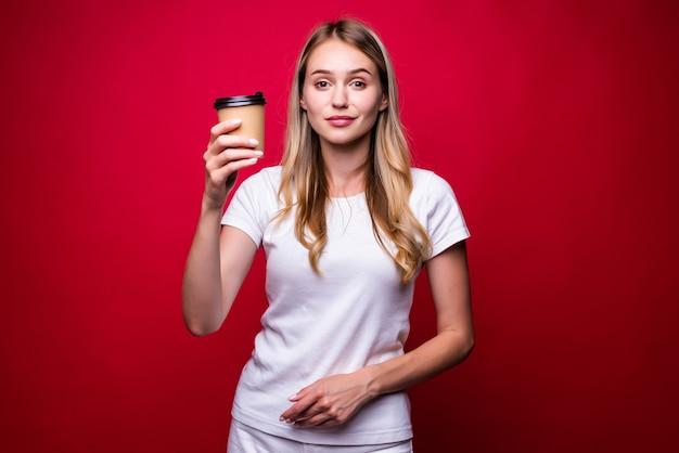 Afbeelding van mooie vrouw met to-go koffie in papieren beker geïsoleerd over rode muur
