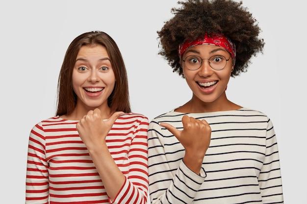 Afbeelding van mooie vrouwen met vreugdevolle uitdrukkingen, breed glimlachen, naar elkaar wijzen met duimen, zich dolgelukkig voelen, gestreepte kleding dragen, model tegen een witte muur. kijk naar mijn vriend, alsjeblieft!